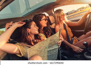 Three female friends enjoying road trip traveling at vacation in the car.