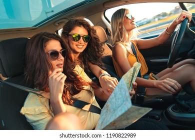 Three female friends enjoying traveling in the car.