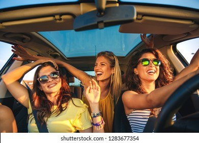 Three female friends enjoying traveling at vacation in the car.