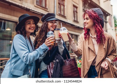 Three female friends having drinks outdoors. Happy women clinking coffee, orange juice and tea cups and laughing by cafe