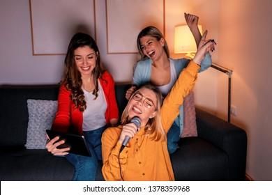 Three female friends having fun playing karaoke at home.