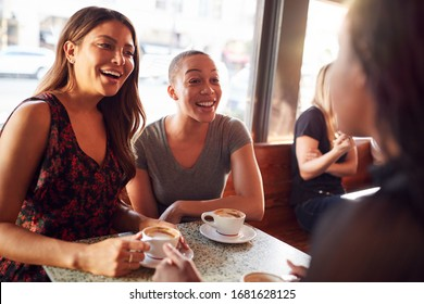Three Female Friends Meeting For Coffee Sitting At Table Together