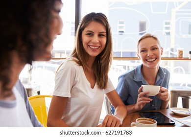 Three Female Friends Meeting In Coffee Shop