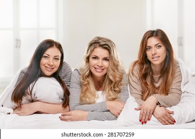 three female friends portrait on the bed on light window background