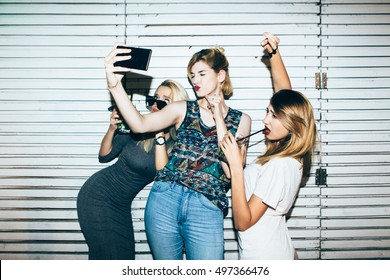 Three female friends posing in front of white wall and taking selfie