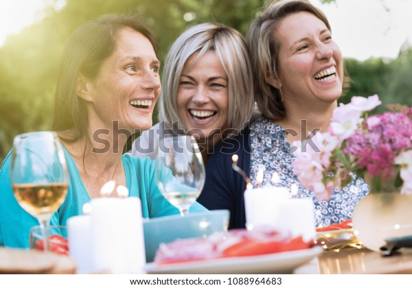 drei Freundinnen in ihren 40ern teilen einen Moment der Mittäterschaft. Sie versammelten sich um einen Tisch im Garten, um ein Essen mit Freunden zu teilen.