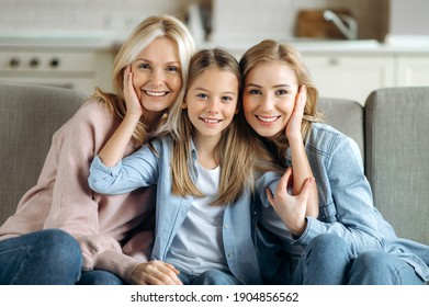 Three female generation. Happy caucasian grandmother, daughter and granddaughter are sitting at home on the couch, hugging, looking at the camera and smiling. Family relationships and values