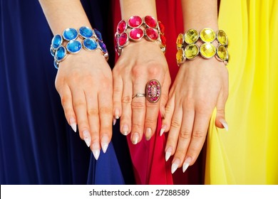 three female hands with similar different color bracelets