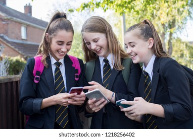 Three Female High School Students Looking At Social Media On Mobile Phones As They Walk To School