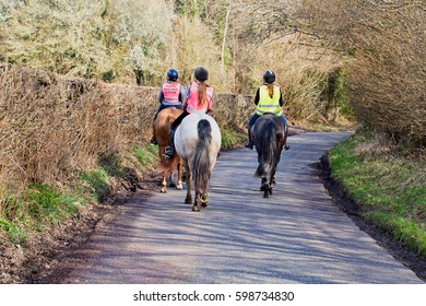 Three female horse-riders on a country lane, wearing safety hats and hi-viz jackets, at mid-distance as the lane bends away to the right.