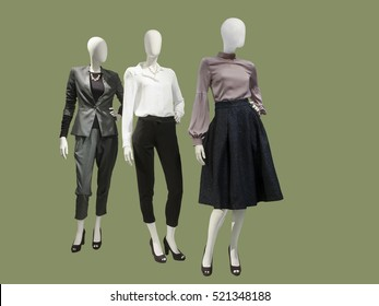 Three female mannequins dressed with fashionable modern clothes, isolated. No brand names or copyright objects.