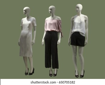 Three female mannequins dressed in fashionable clothes over green background. No brand names or copyright objects.