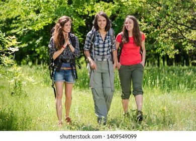 Three female smile tourists walk with backpacks