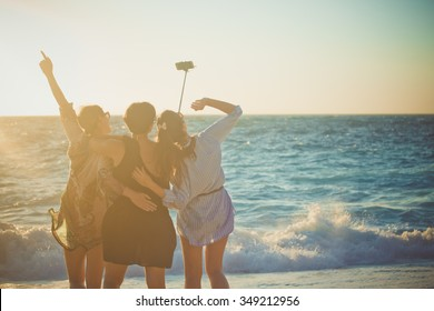 Three female traveler taking selfie at the beach. Back view