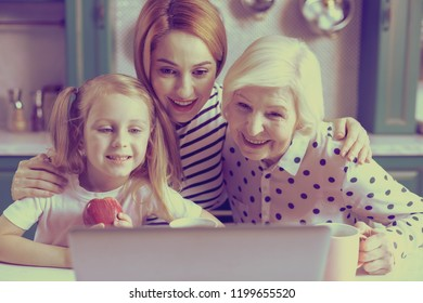 Three females. Amazing funny girl holding apple and staring at screen of her laptop