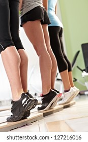 Three females doing calves exercises at the gym. Only legs.