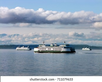 Three ferry boats from the Washington State Ferry system pass each other while crossing Puget Sound