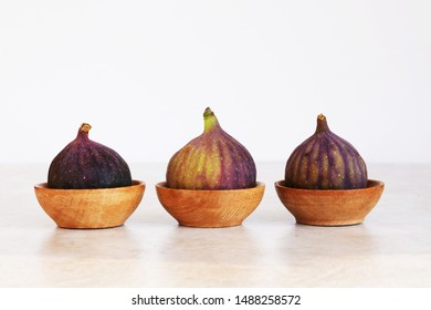 Three fig fruits in a row in small wooden bowls over marbled tabletop. Ficus carica fruits.
