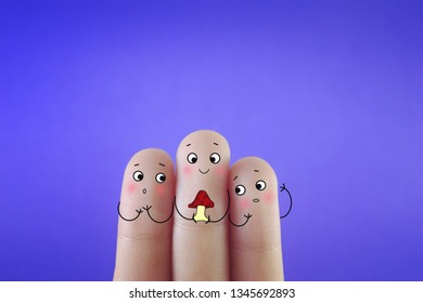 Three fingers decorated as three friends and one of them is holding a mushroom.