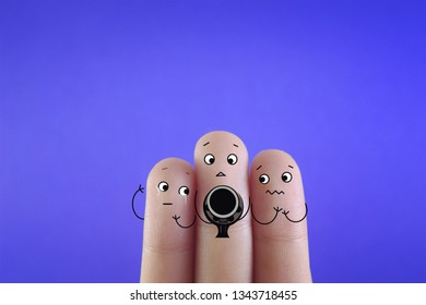 Three fingers decorated as three person decorated as three friends. One of them is holding gun.