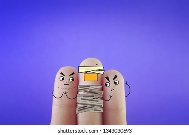 Three fingers decorated as two bad guys kidnapping a man.