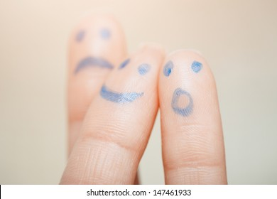 Three fingers with painting of various emotional faces