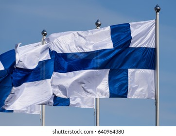 Three Finnish flags flying on sunny spring evening with blue sky in the background