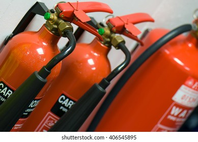 Three fire extinguishers arranged in a row