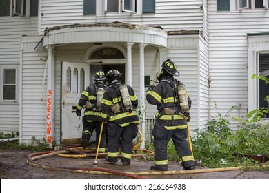 Three Firefighters on Fire Scene Walking into a building