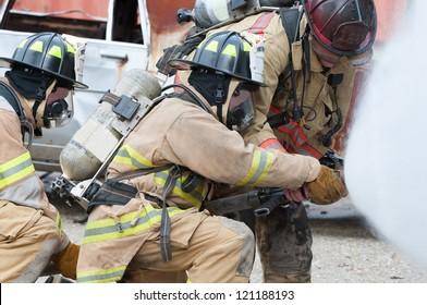 Three firemen extinguishing a car fire.