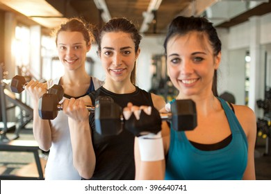 Three fit and beautiful young women lifting weights in a fitness club. Focus on girl in the center.
