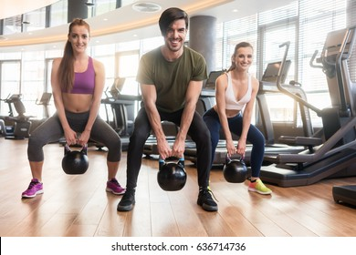 Three fit young people smiling and looking at camera while exercising kettlebell swings during full body workout at the gym