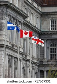 Three flags flying in front of Canadian government building: Flag of Montreal, Quebec and Canada