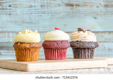 Three flavored cupcakes on wooden background