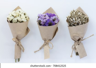 Three flower bouquet on white background. A bouquet of dried flowers wrapped in kraft paper.