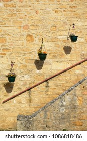 Three flower pots hanging against ancient stone wall above a stairway in old village in Dordogne, France.