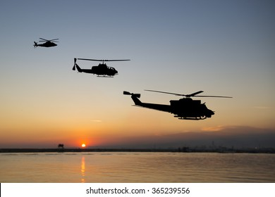 Three flying army helicopters on sunset background