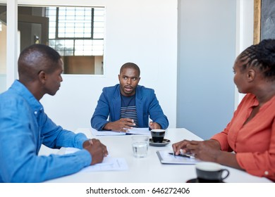 Three focused young African businesspeople sitting together in a meeting at a table in a modern office discussing paperwork