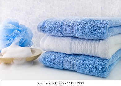 Three fold bath towels, bar of soap and a blue shower sponge./Bath Towels