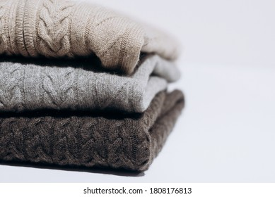 Three folded cashmere knitted sweaters in different shades of gray on white background. three shades of gray. Stack of three sweaters isolated on black background. Knitted wool sweaters.