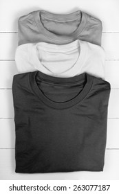 Three folded t-shirts. Converted in black and white
