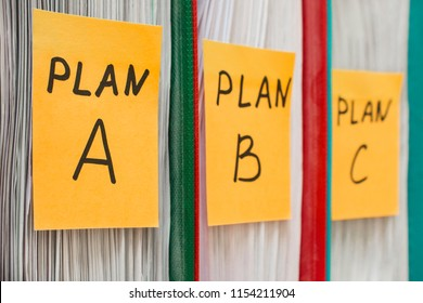 Three folders with stickers, on which plan a, b or c is written. Business planning. A spare option. Difficulties of enterprise management. Decision making, development options. Background in blur.