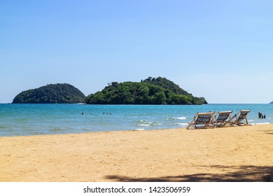 Three folding beach chairs on the beach with sea, bright sky in the background at Koh Mak in Trat, Thailand. Seasonal Vacation. Background with copy space.