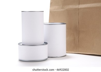 Three food cans with blank white labels in front of a brown paper grocery bag.