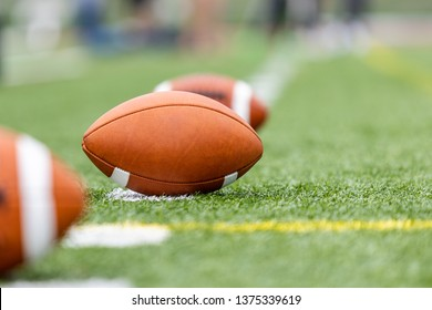 Three football balls on a laying on a green field