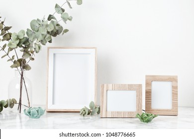 Three frames mockup, front view, with decor elements, flowers and blank copy space over the white wall.