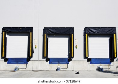 Three freight  loading doors with a set of green and red light to aid driver.