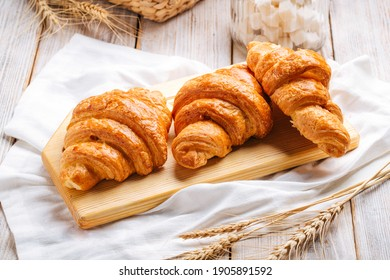 Three french croissants on the wooden cutting board decorated with wheat and napkin