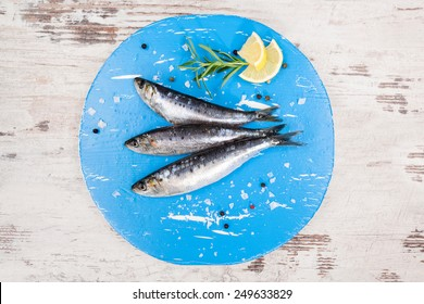 Three fresh anchovy fish on blue round kitchen board on white wooden table, top view. Culinary seafood concept. Delicious healthy eating.