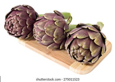 Three fresh artichokes on a cutting board
